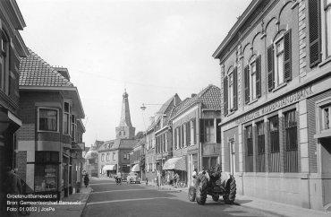 Verleden 1950/1960 - Jan van Schaffelaarstraat in richting Oude Kerk. Links bakkerij Rutgers. Rechts Nederlandsche Middenstandsbank met tractor voor de deur. - Barneveld