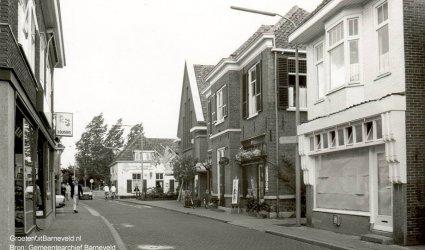 Verleden 1984/1986 - De Nieuwstraat in de richting van de Burgemeester Kuntzelaan. Van links naar rechts: 3 Suisses, firma van de Kleut, café restaurant Het Schaap, in de oude gereformeerde kerk de Veense Tapijthal, schilderswinkel Ten Ham en in het dichtgeplakte pand was gevestigd het Moluks restaurant en catering van de dames Metekohi. - Barneveld