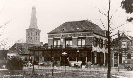 Verleden 1930/1940 - De foto is gemaakt vanuit de tuin van de Westerveldstichting met in het midden Hotel Café Restaurant Hof van Gelderland. Links van het hotel het pand van Tolboom. Rechts het huis van Van den Berg?. Op de achtergrond de toren van de Oude Kerk. - Barneveld