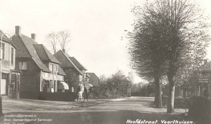 Verleden 1925/1940 - De Hoofdstraat in de richting van Apeldoorn. Rechts een bord met reclame voor garage Visser. Op de achtergrond de brug over de Ganzenbeek. - Voorthuizen
