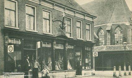 Verleden 1910/1925 - Magazijn 't Anker van de firma D. Romeijn, Manufacturen en bedden. Rechts de Oude Kerk met de overkapping van de botermarkt. - Barneveld